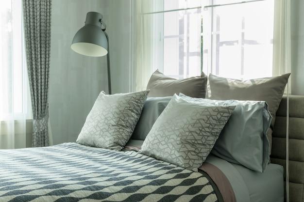 Design de interiores de quarto elegante com almofadas estampadas na cama e candeeiro de mesa decorativo.