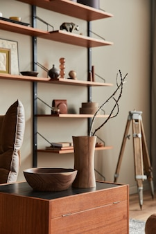 Design de interiores de sala com poltrona marrom, mesa de centro, estante de madeira, livro, porta-retrato, decoração e acessórios pessoais elegantes na decoração da casa.