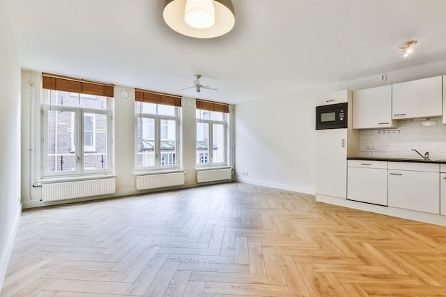 Design de interiores de um apartamento estúdio vazio e espaçoso com grandes janelas, piso laminado e paredes brancas com utensílios de cozinha