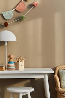 Design de interiores de um elegante quarto infantil com prateleira branca, brinquedos de madeira, acessórios infantis, lâmpada branca, decoração aconchegante e bandeiras de algodão penduradas na parede bege.