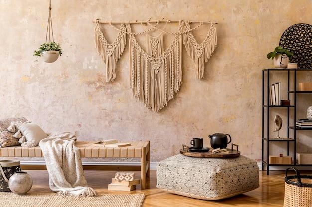 Design de interiores de uma elegante sala de estar com chaise longue, lindo macramê, decoração de vime, plantas, livro, planta, acessórios pessoais elegantes no conceito oriental de decoração para casa.