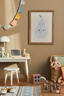 Design de interiores do elegante espaço infantil com mesa branca, laptop de madeira, brinquedos, acessórios infantis, lâmpada, decoração aconchegante e bandeiras de algodão penduradas na parede bege. quadro, armação.