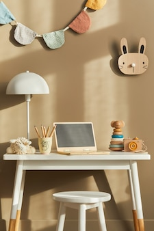Design de interiores do elegante espaço infantil com mesa branca, laptop de madeira, brinquedos, acessórios infantis, lâmpada, decoração aconchegante e bandeiras de algodão penduradas na parede bege.