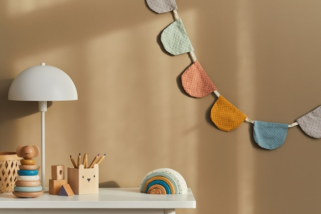 Design de interiores do elegante espaço infantil com prateleira branca, brinquedos de madeira, acessórios infantis, lâmpada branca, decoração aconchegante e bandeiras de algodão penduradas na parede bege.