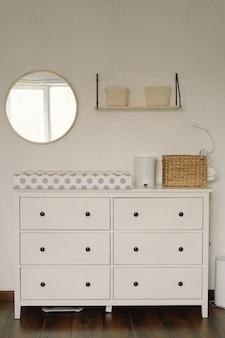 Design de interiores do quarto do bebê. cômoda com trocador e bandeja no berçário. quarto do bebê infantil.