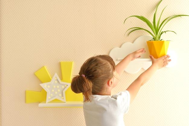 Design de interiores elegante e moderno. casa para o quarto da criança. garota coloca um pote amarelo na prateleira. prateleiras infantis em forma de nuvens brancas em uma parede bege lisa.