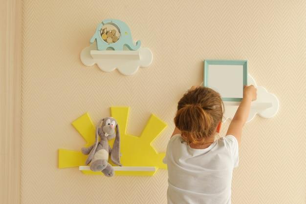 Design de interiores elegante e moderno. sala. girl happy lifestyle coloca uma moldura em uma prateleira prateleiras infantis em forma de nuvens brancas em uma parede bege lisa. prateleiras da moda na sala.