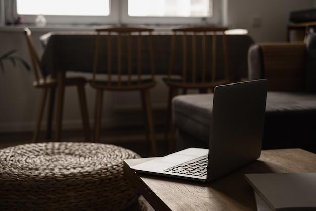 Design de interiores moderno. sala de estar elegante e bem iluminada decorada com mesa de madeira maciça, pufe de rattan, laptop