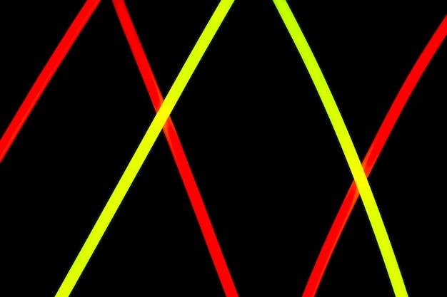 Design de linhas de néon vermelho e amarelo diagonal em fundo preto