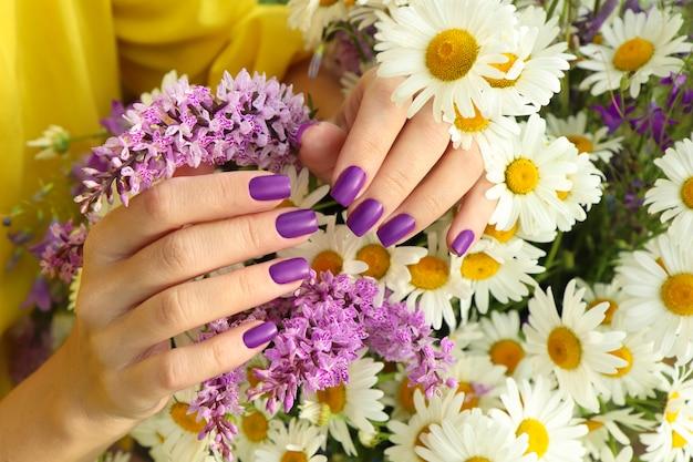Design de manicure com revestimento lilás fosco sobre buquê de margaridas.