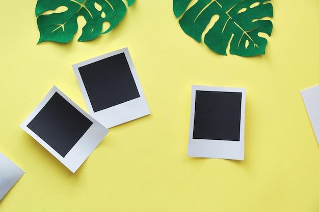 Design de maquete de moldura de foto, plana leigos com três quadros de papel em fundo amarelo com folhas de monstera exótica