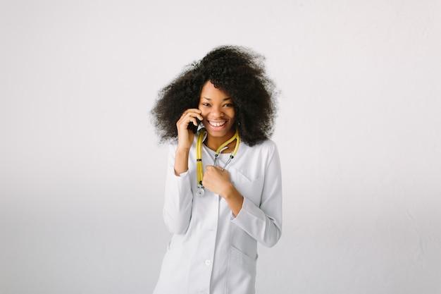 Design de propaganda de medicina. jovem menina bonita da menina afro-americana no jaleco branco com estetoscópio e pasta no hospital. um fundo amplo impessoal. falando no telefone