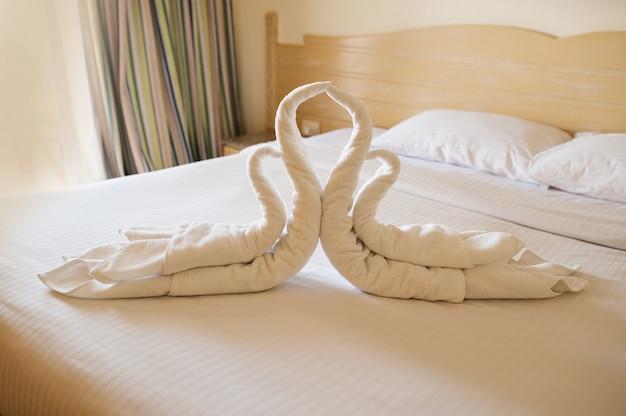 Design de quarto com cisnes da decoração de toalha na cama
