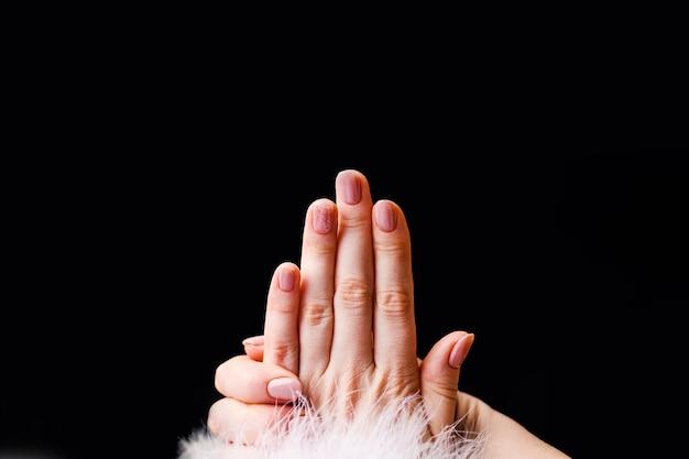 Design de unhas. mãos com manicure rosa brilhante no preto