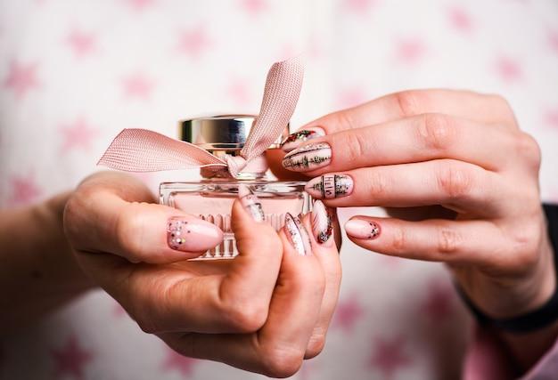 Design de unhas. mãos com manicure rosa e verde brilhante
