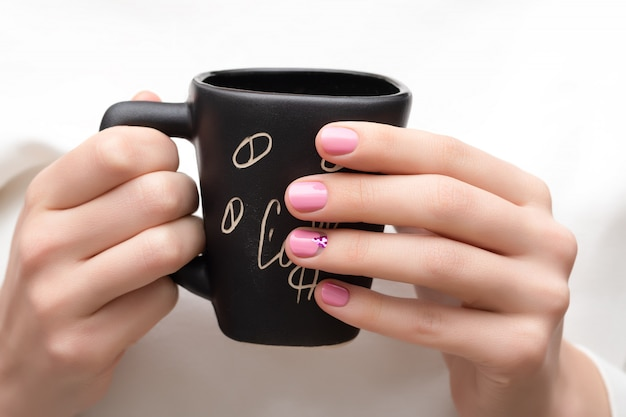 Design de unhas rosa. femininas mãos segurando um copo preto.