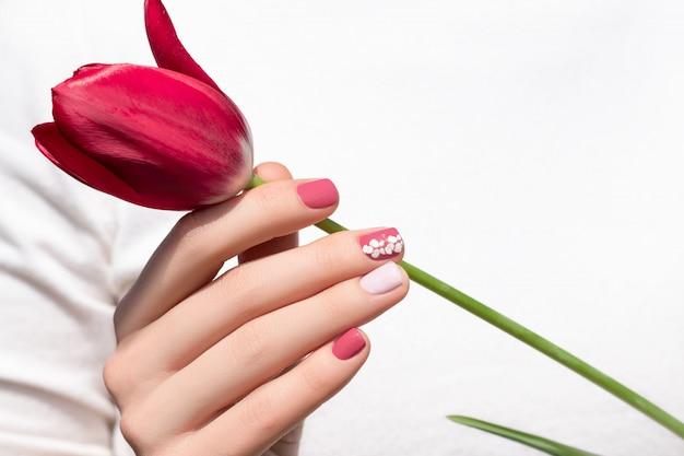 Design de unhas rosa. mão feminina com manicure rosa segurando flor tulipa