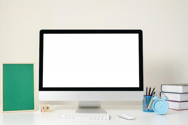 Design do local de trabalho com tela de computador branco está de pé sobre uma mesa em um escritório