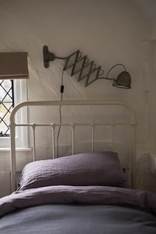 Design elegante quarto com travesseiros escuros na cama e uma lâmpada decorativa preta.