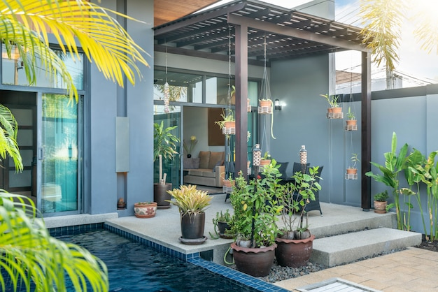 Design exterior e interior mostrando villa piscina tropical com jardim verde, com cama de sol e céu azul