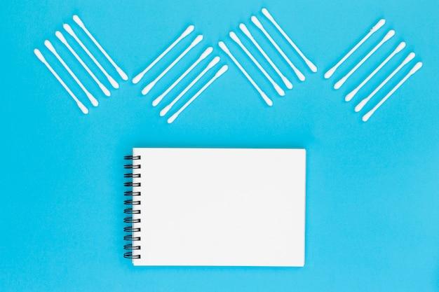Design feito com cotonetes no bloco de notas espiral em branco sobre fundo azul