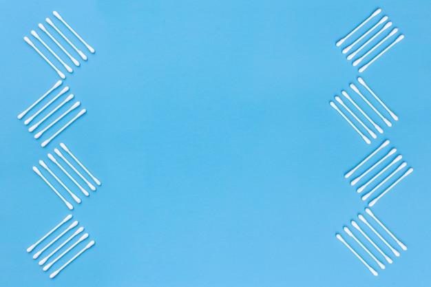 Design feito com cotonetes no lado de fundo azul