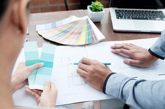 Design gráfico e amostras de cores e canetas em uma mesa. desenho arquitetônico com ferramentas de trabalho e acessórios.
