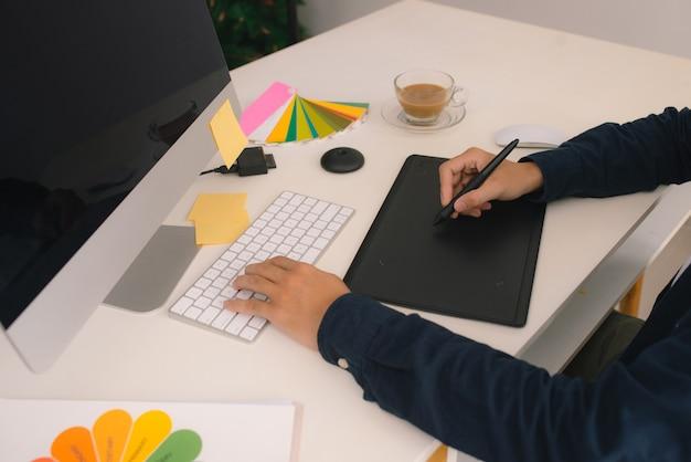 Design gráfico, impressão, publicidade designer gráfico trabalhando com digitalizador, lupa, paleta pantone