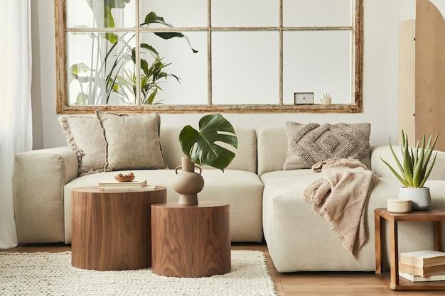 Design interior da sala de estar com sofá bege modular elegante, mesas de centro de madeira, plantas, travesseiros, xadrez, divisória neutra, decoração e acessórios elegantes.