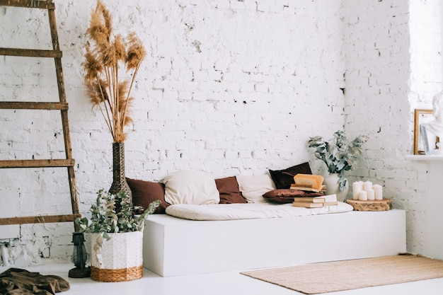 Design interior de sala de estar bem iluminada com paredes brancas e banco sofá com almofadas