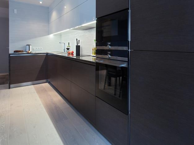 Design interior de uma cozinha de alta tecnologia com armário escuro