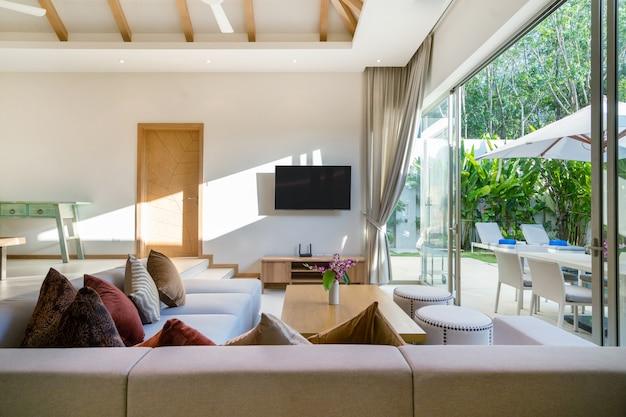 Design interior e exterior da sala de estar com vista para a piscina em vivenda de luxo