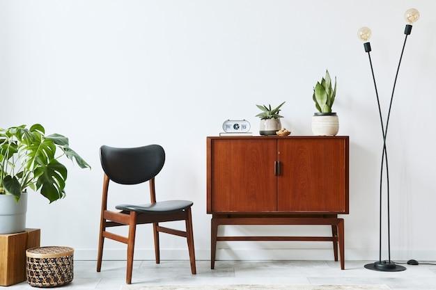 Design interior elegante de sala de estar com cômoda retro de madeira, cadeira, algumas plantas, cesta de vime, decoração, lâmpada, relógio e acessórios pessoais elegantes. copie a parede branca do espaço.