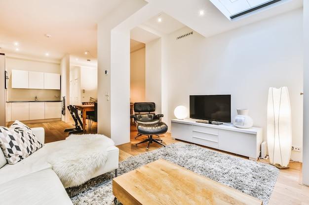 Design interior elegante de sala de estar com móveis claros e sofá e carpete macios e confortáveis e com tv no armário em apartamento moderno com cozinha aberta e paredes e colunas brancas