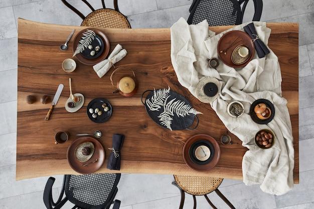 Design interior elegante de sala de jantar com mesa de madeira de nogueira, cadeiras retrô, talheres, pratos, toalha de mesa, bule, comida, decoração e acessórios elegantes. chão de cimento. vista do topo.