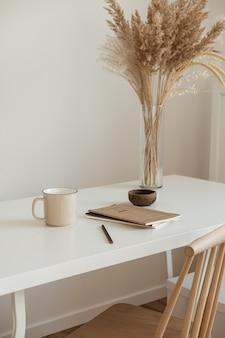 Design interior estético mínimo do espaço de trabalho do escritório. caneca, caderno, buquê floral de grama dos pampas em uma mesa branca contra uma parede branca