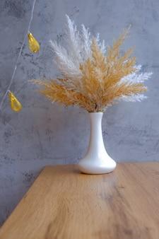 Design interior minimalista escandinavo, vaso branco com juncos na mesa de madeira, parede de cimento e guirlanda