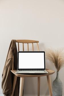 Design interior moderno de casa com cadeira de madeira com camisa e grama dos pampas em um vaso contra a parede branca
