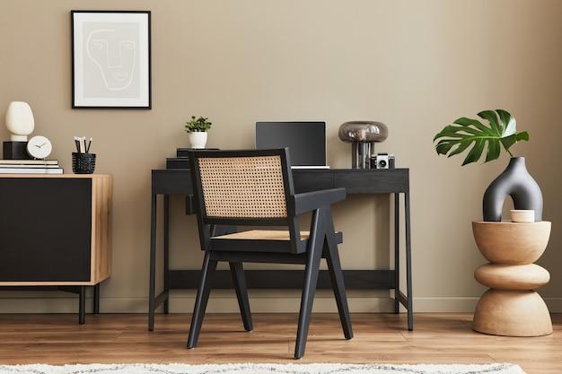 Design interior moderno de espaço de escritório em casa com cadeira elegante, mesa, cômoda, moldura preta, lapatop, livro, material de escritório e acessórios presonais elegantes na decoração da casa.