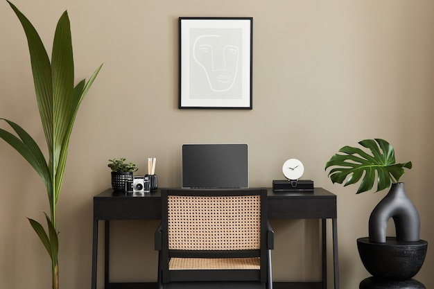 Design interior moderno de espaço de escritório em casa com cadeira elegante, mesa, cômoda, moldura preta, lapatop, livro, organizador de mesa e acessórios presonais elegantes na decoração da casa.