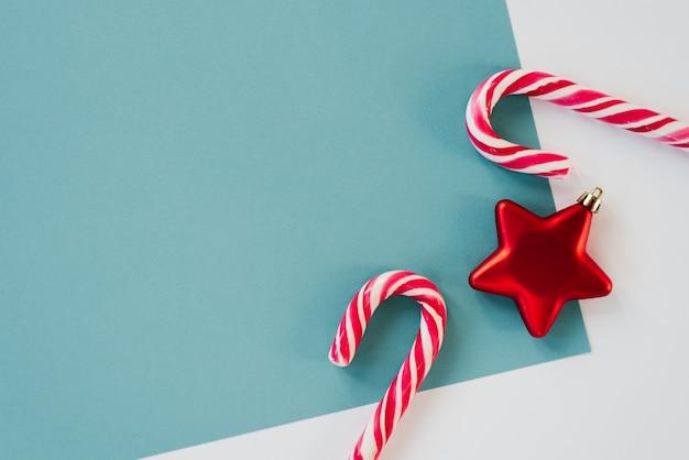 Design minimalista para cartão de natal e ano novo com copyspace. estrela vermelha do brinquedo da árvore de natal e dois bastões de doces nos fundos brancos e azuis. tendência e estilo