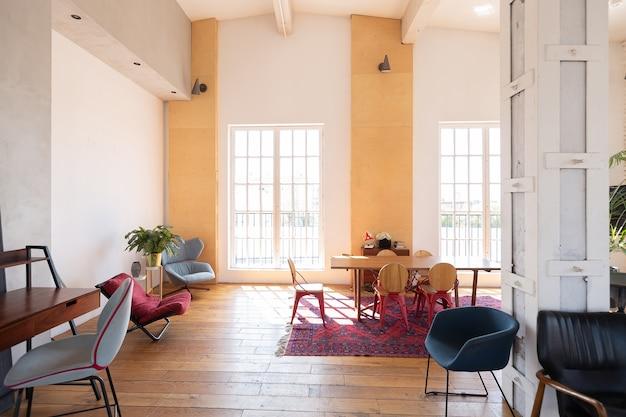 Design moderno de uma enorme sala branca e iluminada com dois sofás vermelhos e muitas janelas grandes. cheio de sol. teto alto e parquet de madeira