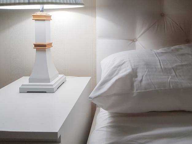 Design moderno e luxuoso de um quarto bem iluminado com mesa de cabeceira, abajur e um travesseiro na cama, preparando-se para dormir