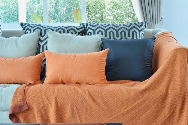 Design moderno sala de estar com sofá de tweed marrom e laranja e travesseiros pretos