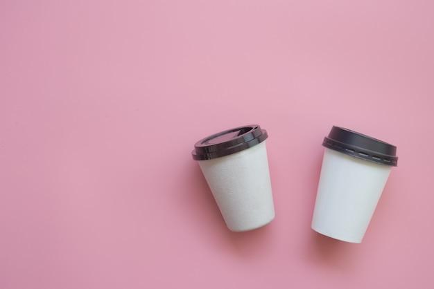 Design plano leigo de 2 xícaras de café quente em pastel rosa