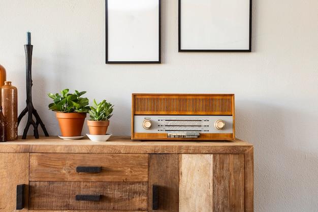Design retrô da sala de estar com armário e rádio, juntamente com plantas verdes e moldura em branco, parede branca