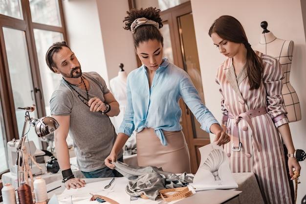 Designer africano toca material. grupo de três pessoas no estúdio de design. homem e duas mulheres estão tomando decisões