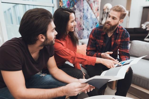 Designer ajuda um homem e uma mulher a escolher amostras de cores
