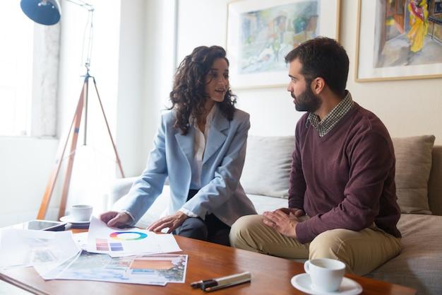 Designer amigável e cliente discutindo a cor da parede