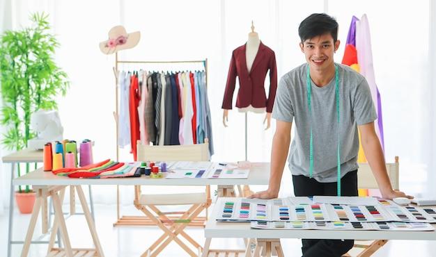 Designer asiático masculino sorridente com fita métrica no pescoço, em pé perto da mesa com amostras variadas